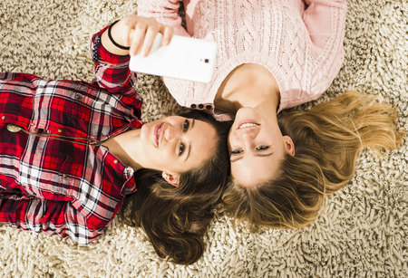 Two female friends taking a selfie with smartphone at home LANG_EVOIMAGES
