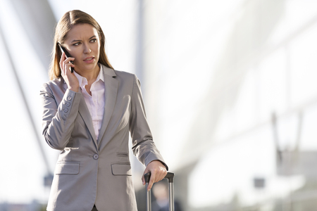 Businesswoman on cell phone outside airport building