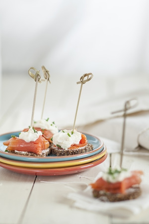 Skewered appetizers made of German rye bread, salmon and horseraddish cream sauce