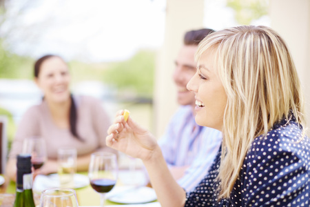 Smiling woman having dinner with friends