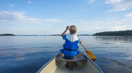 Finland, Karelia, canoeing boy on lake Pielinen