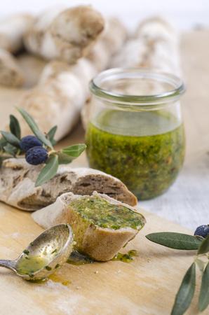 Sliced home-baked baguette with fresh basil pesto on wooden board LANG_EVOIMAGES