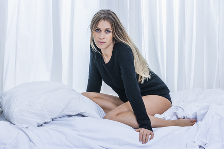 Blond woman sitting on bed in front of white curtain
