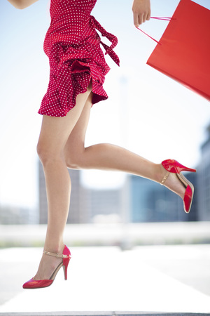 Legs of red dressed woman with shopping bag LANG_EVOIMAGES