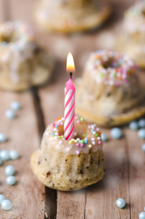 Miniature birthday cake with lighted candle