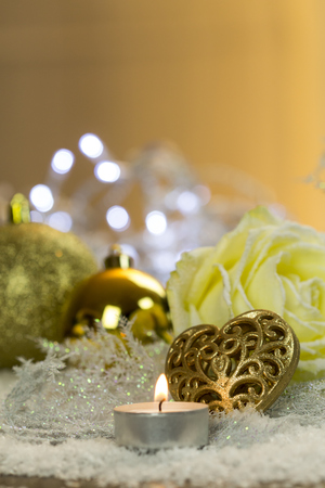 Christmas decoration with tea light, Christmas baubles and rose blossom on artifical snow