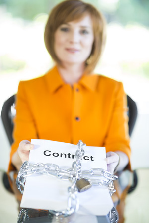Businesswoman holding contract locked with chain