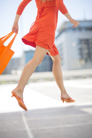 Orange dressed woman with shopping bag