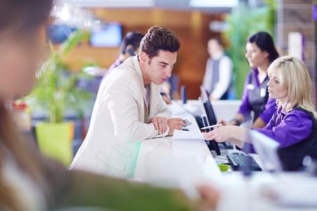 Businessman registering at hotel reception