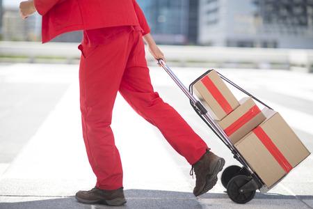 Red dressed parcel deliveryman with parcels