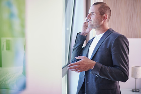 Businessman on cell phone looking out of hotel room window