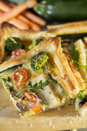 Piece of vegetarian quiche with different vegetables