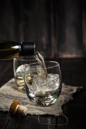 Pouring whisky into a tumbler with ice