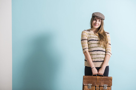 Smiling female teenager with old leather brief case