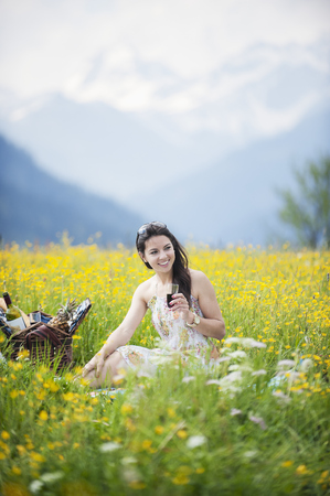 Young woman having picnic on alpine meadow LANG_EVOIMAGES