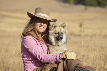 USA, Wyoming, cowgirl with her dog