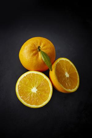 Orange and two halves of an orange on dark ground