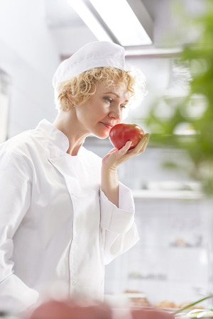 Female chef in kitchen smelling at tomato