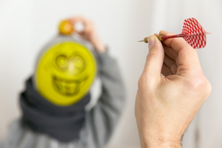 Hand with dart aiming at balloon person