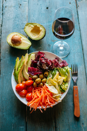 Mixed salad, sliced avocado and glass of red wine