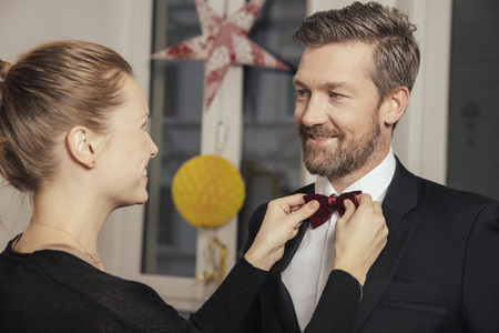Couple preparing for New Years Eve party, fastening bow tie