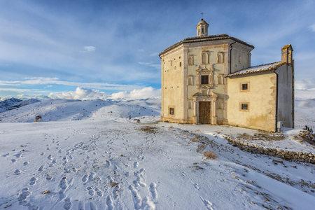 Italy, Abruzzo, Gran Sasso e Monti della Laga National Park, The small church of Santa Maria della Pieta in Rocca Calascio at sunset in winter