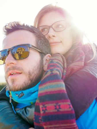 Germany, Stuttgart, portrait of young couple at backlight with reflecting of burial chapel on sunglasses