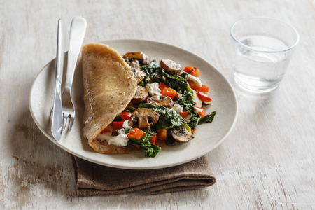 Wholemeal buckwheat spealt wheat pancake, filled with spinach, bell pepper and mushroom on plate