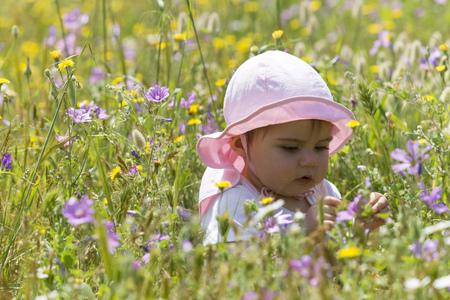 Baby girl sitting in flower meadow
