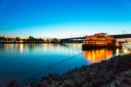 Germany, Bonn, view to Rhine river with lighted restaurant ship LANG_EVOIMAGES