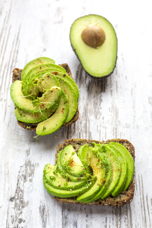 Protein bread garnished with sliced avocado, cress and chili powder LANG_EVOIMAGES