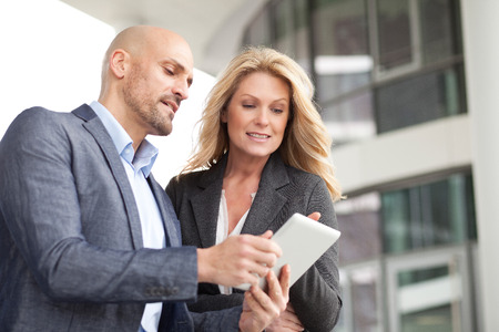 Businessman and businesswoman with digital tablet outdoors LANG_EVOIMAGES