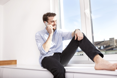 Young man sitting on sideboard telephoning with smartphone while looking through window