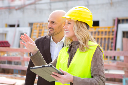 Woman with hard hat talking to man on construction site LANG_EVOIMAGES