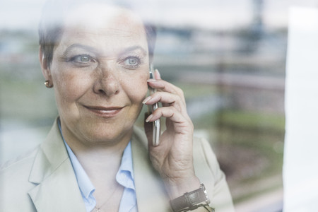 Businesswoman on cell phone behind windowpane