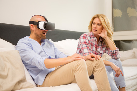 Man sitting on couch at home wearing Virtual Reality Glasses while his wife watching him