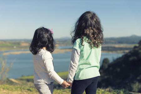 Spain, Burujon, back view of two little girls looking at a lake