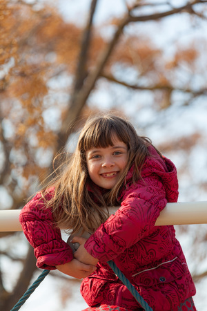 Portrait of smiling little girl climbing on playground equipment LANG_EVOIMAGES