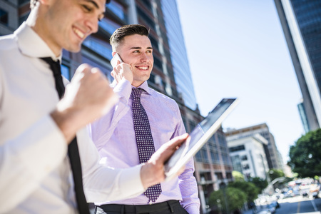 Two businessmen outdoors with tablet and cell phone