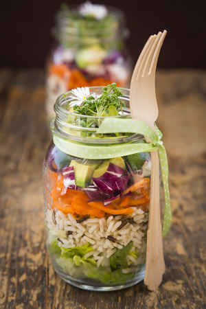 Springtime salad in glasses, lettuce hearts, radicchio, avocado, carrot, zucchini, wild rice and cress, daisy