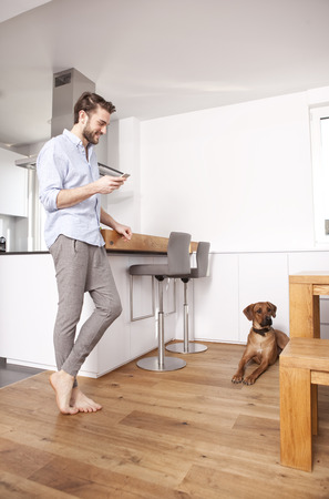 Man with his Rhodesian Ridgeback in the kitchen