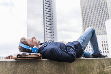 Young businessman lying on wall listening music with headphones LANG_EVOIMAGES