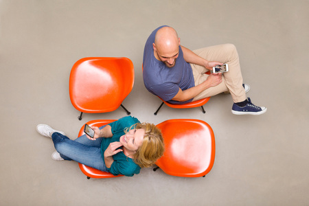 Man and woman sitting on chairs using smart phones