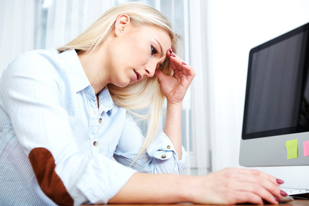 Overstressed blond woman sitting at her desk