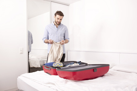 Young man in a hotel room packing his suitcase