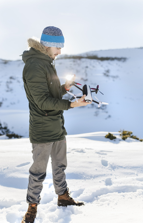 Spain, Asturias, man flying drone in snowy mountains LANG_EVOIMAGES