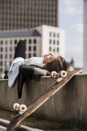 Young woman with skateboard resting on wall