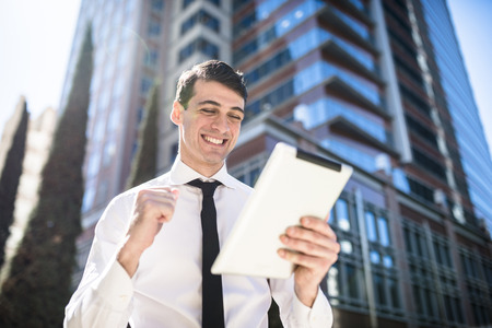 Happy businessman outdoors with tablet clenching his fist LANG_EVOIMAGES