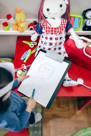 Top view of little girl drawing her doll