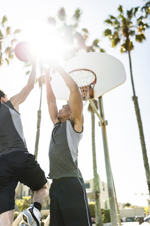 Two young men playing basketball on an outdoor court LANG_EVOIMAGES